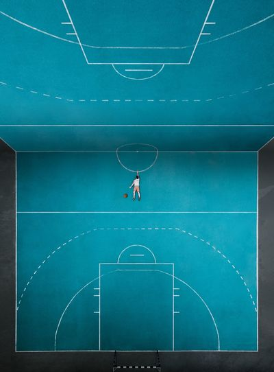 Digital composite image of man lying on basketball court