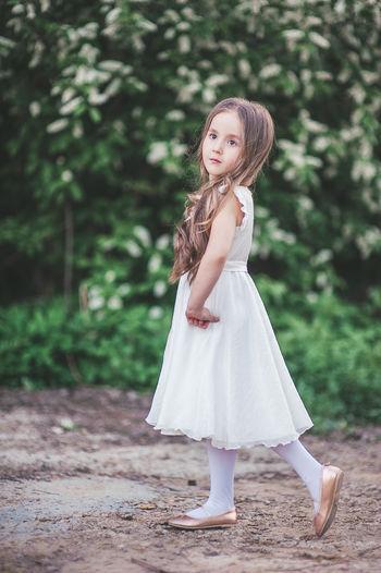 Full length of girl standing against tree