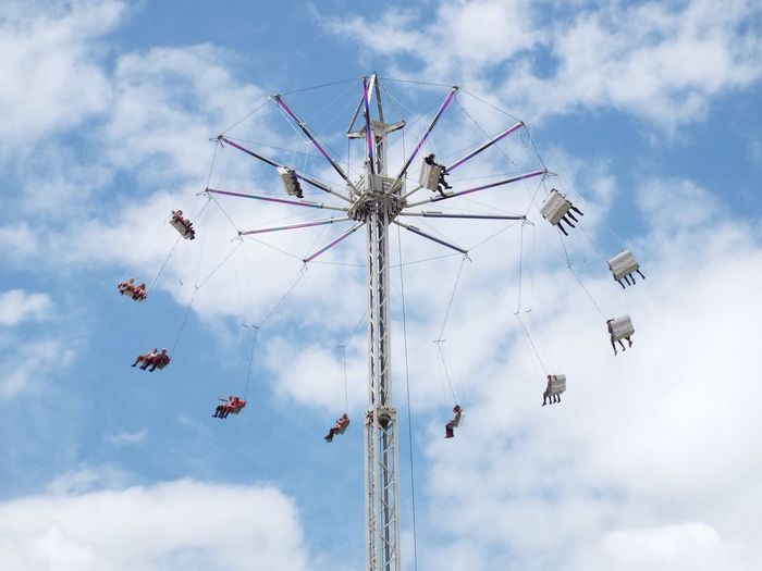 Low angle view of people on chain swing ride
