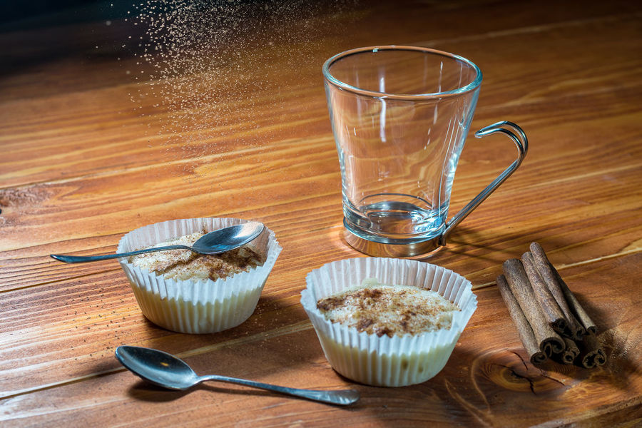 Two cups of rice pudding with cinnamon sticks on a wooden table Pudding Rice Bowl Cinnamon Close-up Cupcake Dessert Food Food And Drink Freshness Indoors  No People Sticks Sutlija Sutlijas Sweet Sweet Food