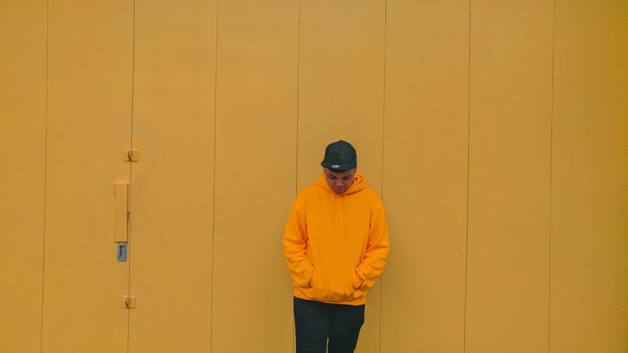 Young man standing against yellow wall