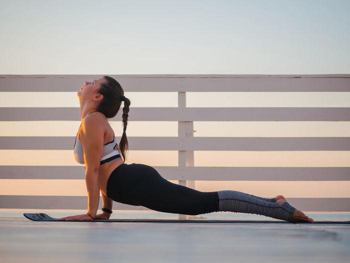 Full Length Of Woman Doing Yoga On Promenade During Sunrise