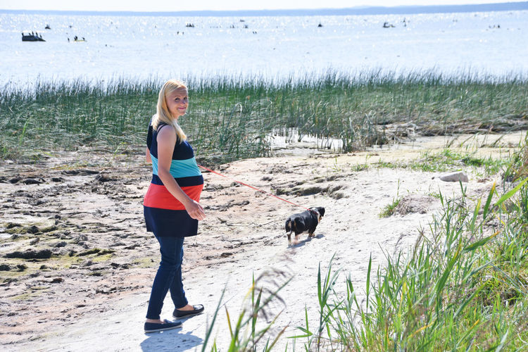 Full length portrait of pregnant woman with dog walking on land