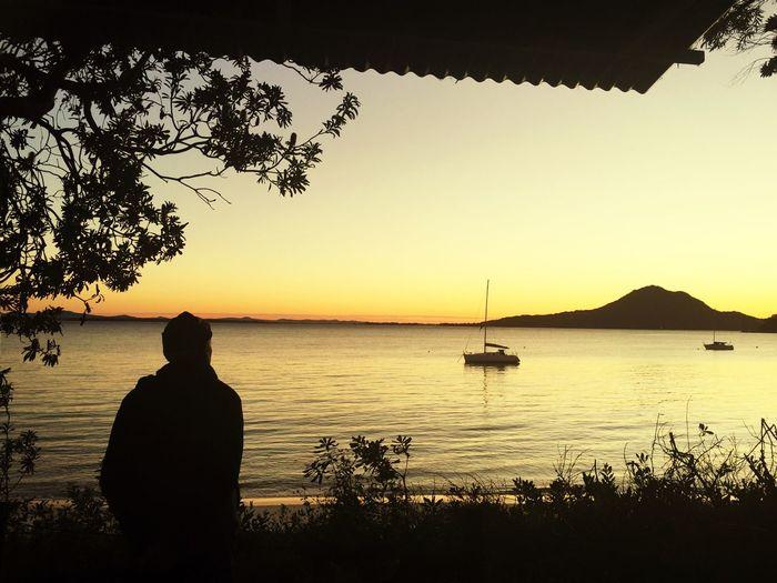 Silhouette man fishing in lake against sunset sky