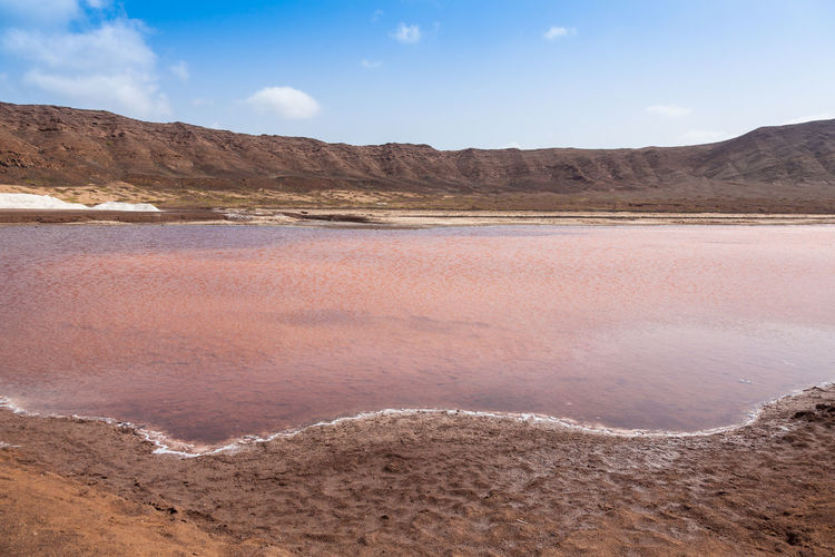 Scenic view of lake on arid landscape against sky