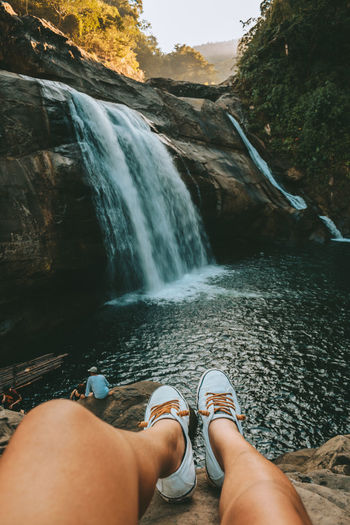 Low section of woman on rock against waterfall