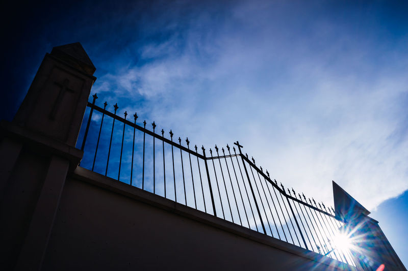 Low angle view of illuminated fence against blue sky