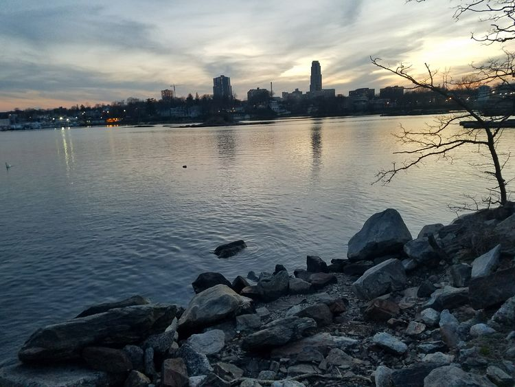 Dusk at Five Islands Park, New Rochelle. I decided to eat pizza over there c: . (4/23/2018) City Cityscape Urban Skyline Water Skyscraper Sunset Sea Downtown District Reflection Sky Seascape Rocky Coastline