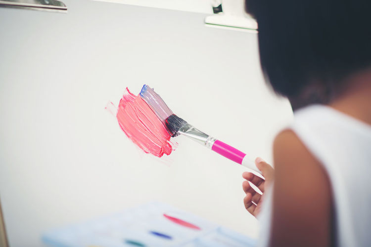 Cropped image of girl painting on canvas