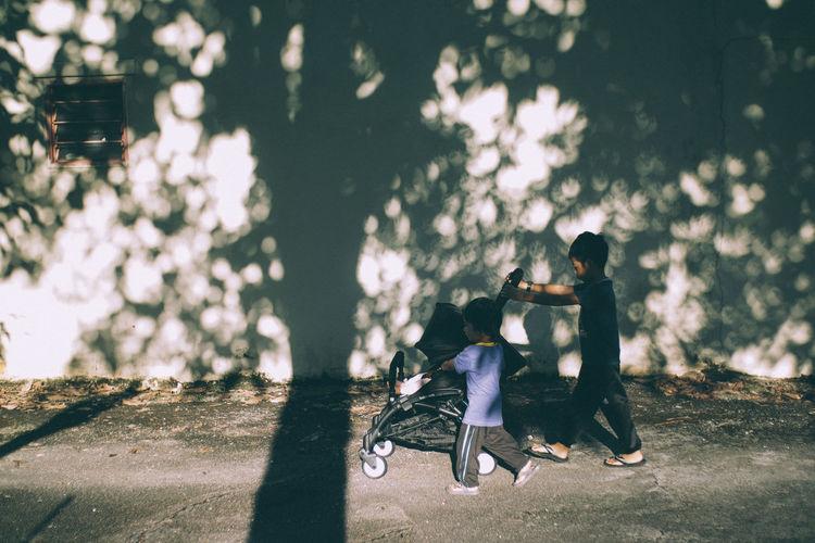 Siblings pushing baby carriage on footpath