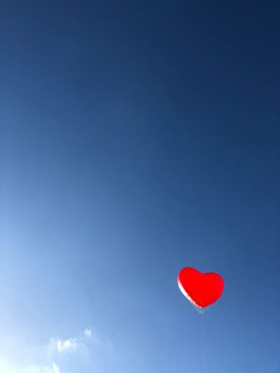 Low angle view of red heart shaped balloon flying against blue sky
