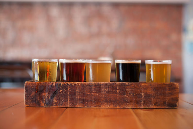 Close-Up Of Various Beer Glass In Wooden Tray On Table