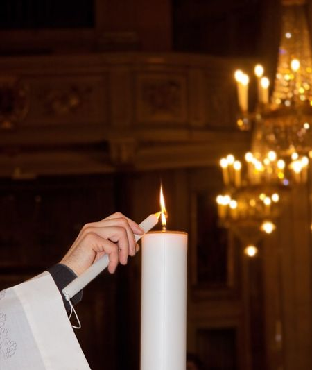 A catholic priest lighting a candle in an italian church during a baptism