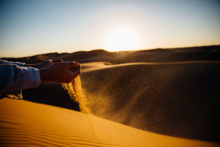 Cropped image of hand pouring sand at desert against sky