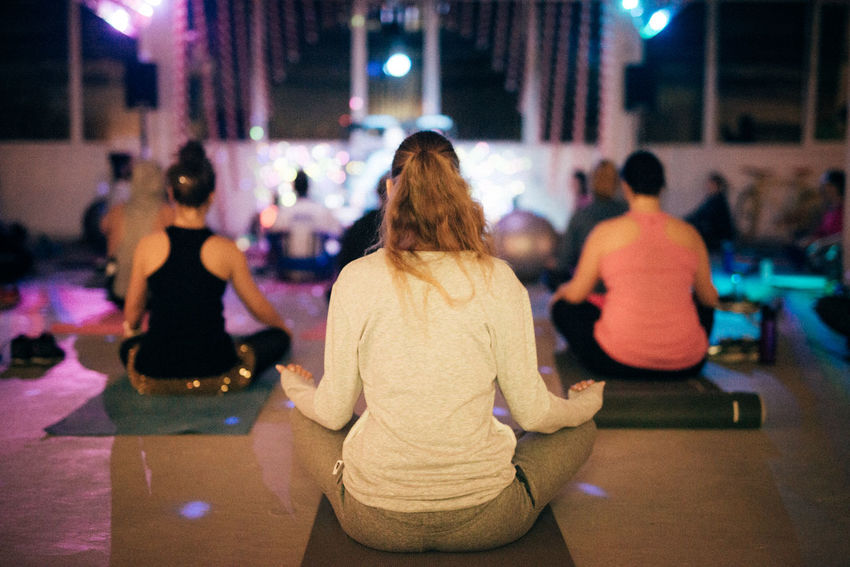 Meditating Meditation Meditation Place OM Relaxing Yoga Yoga Pose Focus On Foreground Illuminated Incidental People Indoors  Large Group Of People Lifestyles Night People Real People Rear View Relaxation Sitting Women Young Adult