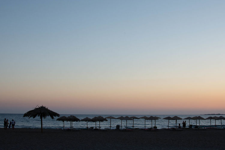 Scenic view of beach against clear sky during sunset