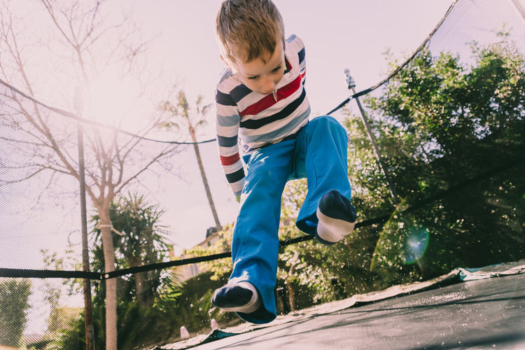 Low angle view of boy jumping at park