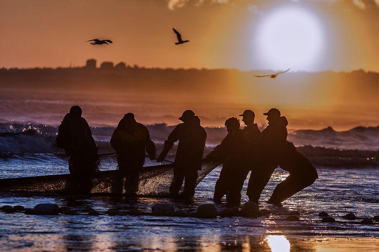 Fishermen Pulling Net From Sea Against Sky During Sunset