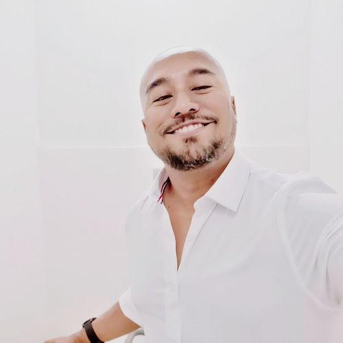 Portrait Of Smiling Man Against White Wall
