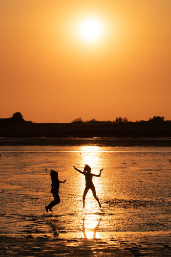Sky Silhouette Sunset Water Two People Sun Orange Color Men Real People Lifestyles Leisure Activity Nature Beauty In Nature Reflection Togetherness Scenics - Nature People Sunlight Sea Outdoors