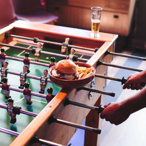 High angle view of burgers in container by man playing foosball