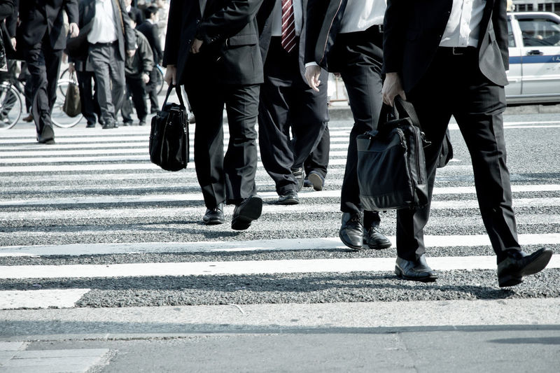 Low section of business people walking on road