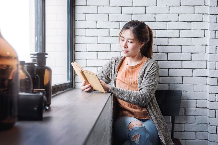 Young woman reading book while sitting on chair by window