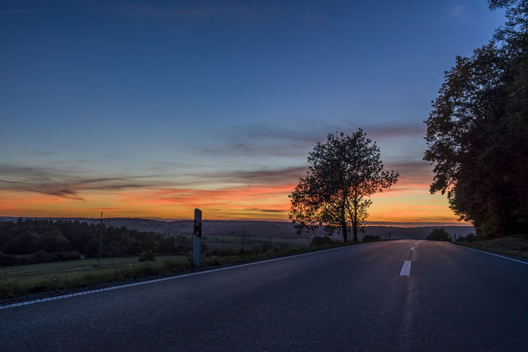 EyeEm Nature Lover Sunset_collection Beauty In Nature Cloud - Sky Diminishing Perspective Direction Dividing Line Empty Road Eyeemgermany Nature No People Orange Color Outdoors Plant Road Scenics - Nature Sign Sky Street Sunset The Way Forward Tranquil Scene Tranquility Transportation vanishing point