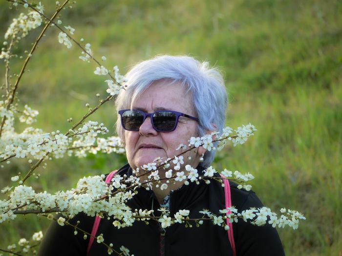 Senior woman looking away by flowers blooming in park