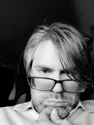 Low angle portrait of mid adult man wearing eyeglasses in darkroom