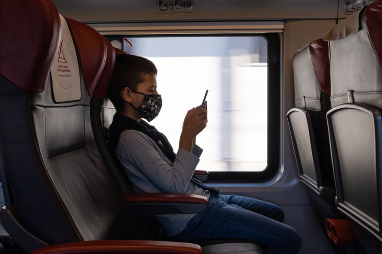 Young boy traveling by train and looking a smart phone. he wears a protective face mask.