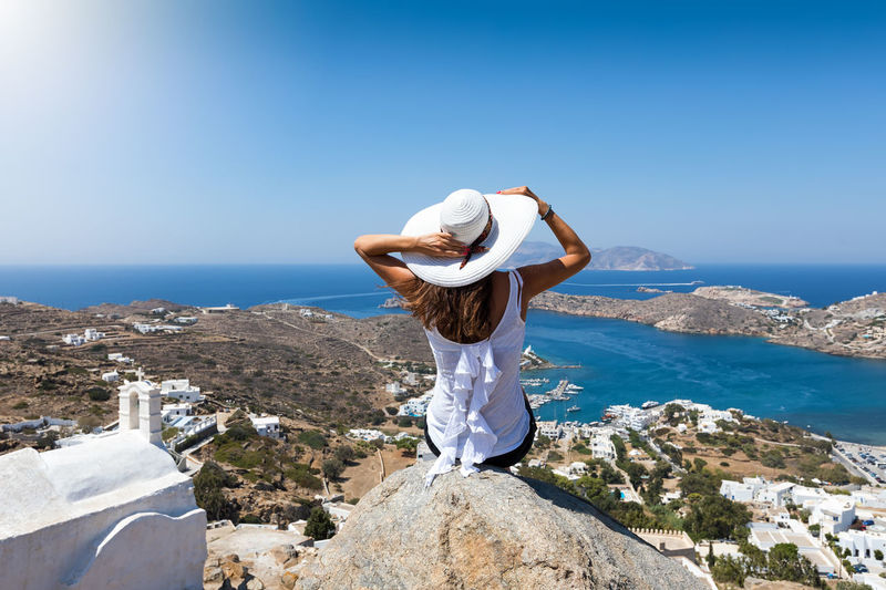 Attractive traveller woman sits on a rock and enjoys the view over the Chora of Ios, Cyclades, Greece Aegean Sea Chora Ios Greece Panorama Tourist Casual Clothing Day Greece Hat Island Leisure Activity Lifestyles Looking At View Mountain One Person Real People Rear View Scenics - Nature Sea Sky Summer Sunlight Travel Destinations Traveller Water It's About The Journey