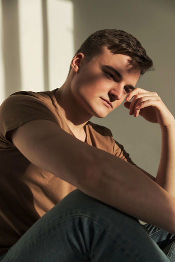 Young man looking away while sitting at home