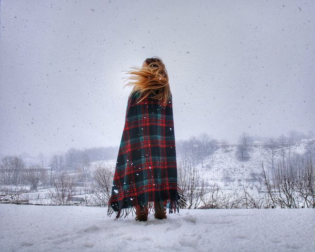 Woman Wrapped In Blanket Standing On Snow Covered Landscape Against Sky