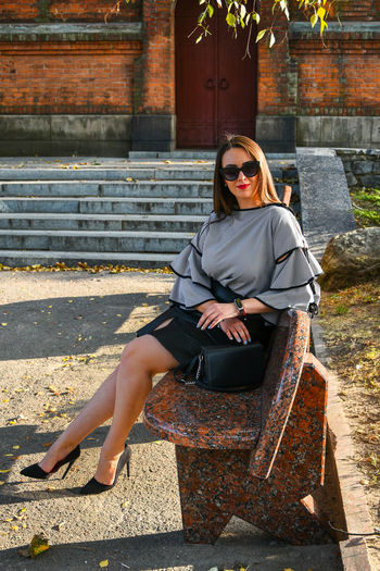 Portrait of young business woman sitting outside. girl in blouse and skirt on high heels. brunette