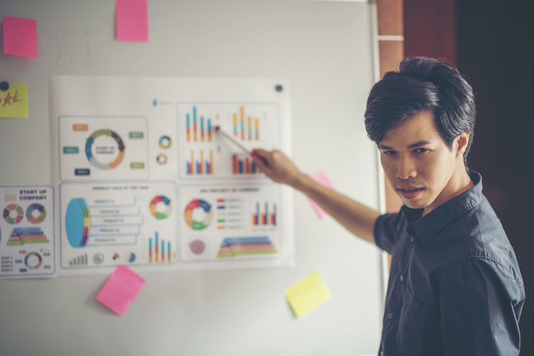 Confident businessman planning strategy over graphs