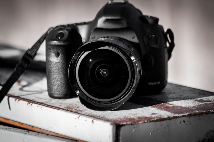 Close-up of camera on table Technology Photography Themes Camera - Photographic Equipment Close-up Focus On Foreground Lens - Optical Instrument No People Camera Photographic Equipment Indoors  Equipment Metal Still Life Single Object Digital Camera Security Lens - Eye Table Black Color Antique