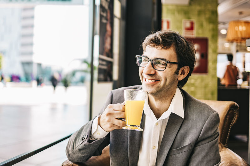 Smiling businessman drinking juice at restaurant