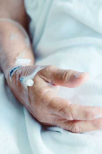 Cropped image of woman wearing iv drip in hospital