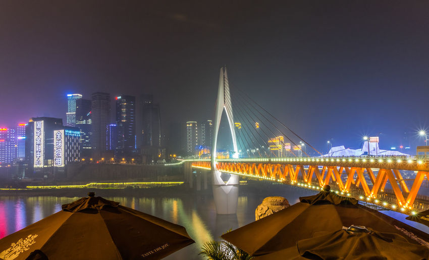 Illuminated bridge over river against buildings at night