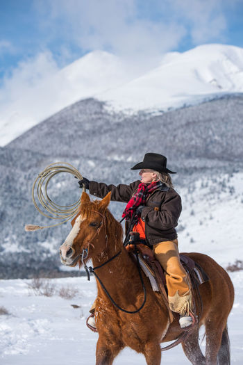 Feb 2019 - Music Meadows Ranch Winter Colorado Snowcapped Mountain Domestic Animals Cowgirl Cowboy Cowboy Hat Chaps Lassoing Rope Ranch Life Domestic Animal Animal Themes Horse Snow Livestock Cold Temperature Real People One Person Activity Riding Outdoors Working Animal Herbivorous Warm Clothing One Animal Mammal Vertebrate