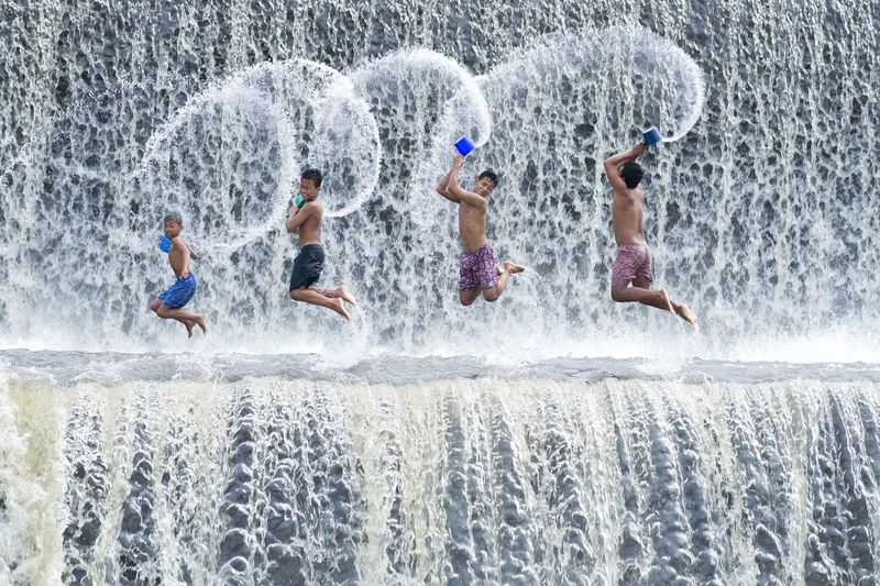 Boys were having fun by playing water in an artificial dam on the Tukad Unda dam, Bali Indonesia Active Balinese Dam Day Enjoyment Fall Formation Four Boys Friendship Fun Happiness ♡ INDONESIA Joy Leisure Activity Lifestyles Outdoors Playing River Spillway Splash Traditional Travel Destinations Tukad Unda Dam Water Waterfall