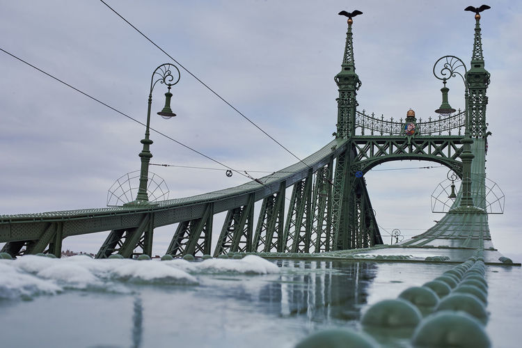 Low angle view of suspension bridge over river during winter