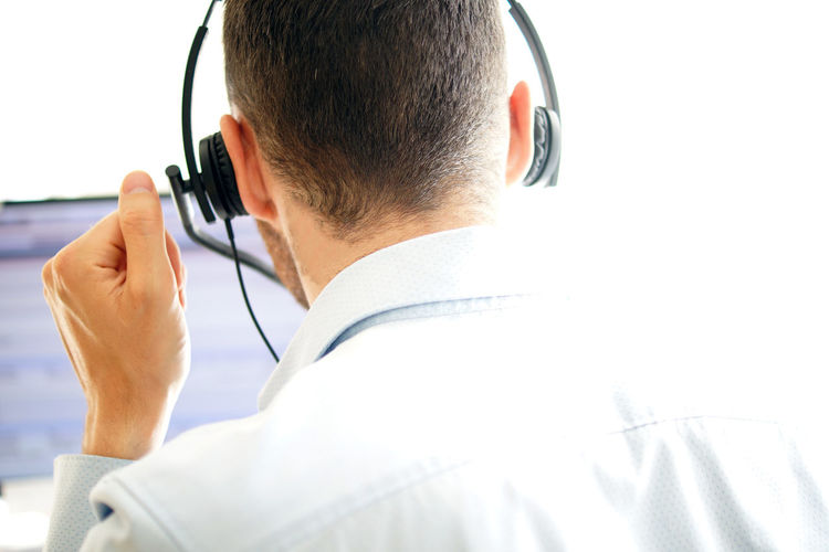 Rear view of male customer service representative wearing headset in call center