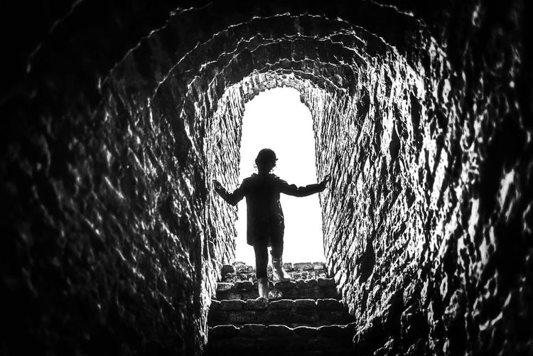 Rear view of silhouette boy standing in tunnel