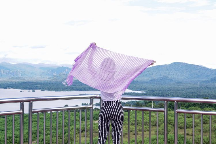 Rear view of woman standing with scarf by railing against sky