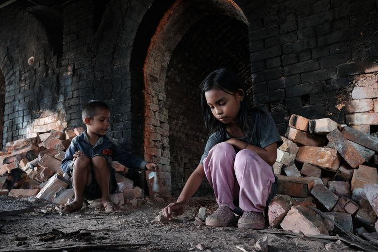 Siblings against brick wall