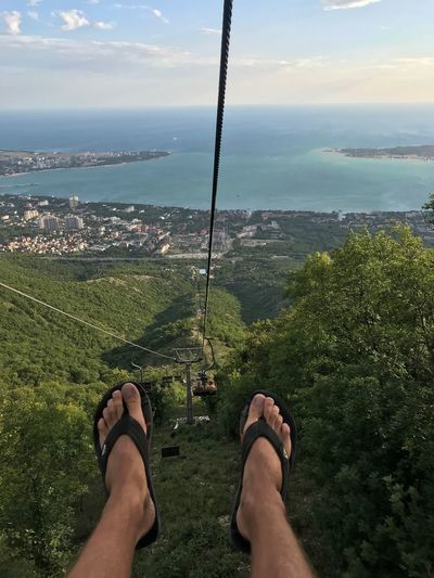 Low Section Of Man Zip Lining Against Sky