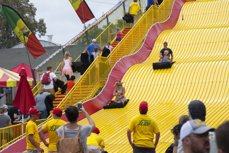 A couple takes photos of their daughters while riding the Giant Slide at the Minnesota State Fair in August of 2018 2018 Children Couple Family Fun Minnesota Mother St Paul State Fair Taking Photos Caucasian Daughter Editorial  Entertainment Father Giant Slide People Summer Yellow