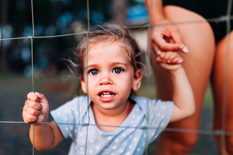 Child Childhood Innocence One Person Portrait Focus On Foreground Real People Cute Front View Emotion Casual Clothing Looking At Camera Women Holding Young Happiness Smiling Baby Positive Emotion Close Up Little Girl Fence Freedom Kidnapping Scared A New Perspective On Life